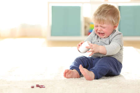 Sad baby crying in danger after eating some pills from a bottle on the floor at home Stock Photo