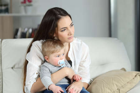 Sad woman looking away with her baby sitting on a couch in the living room at home