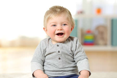 Front view portrait of a happy baby boy smiling looking at you sitting on the floor