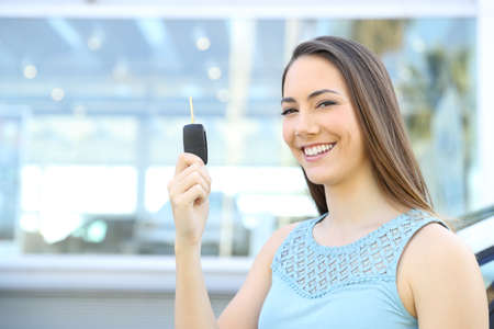 Satisfied owner showing keys after buy in a car dealership Stock Photo - 95174954