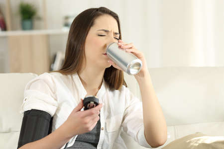 Woman suffering a low blood pressure drinking sweet soda sitting on a couch in the living room at home 스톡 콘텐츠