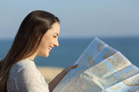 Side view portrait of a happy tourist reading a map on the beach