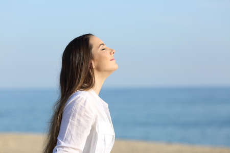 Side view portrait of a woman relaxing breathing fresh air on the beach