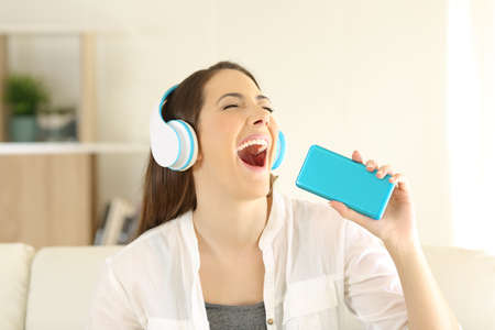 Happy teen singing and listening to music with a smartphone and headphones sitting on a couch in the living room at home
