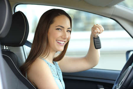 Happy owner sitting inside her car holding keys and looking at camera