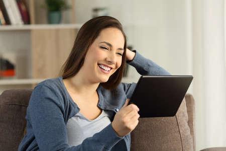 自宅のリビングルームのソファに座っているタブレットでメディアを見て幸せな主婦 写真素材