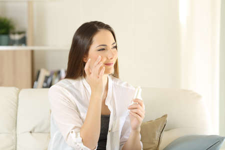 Portrait of a beauty woman moisturizing her face skin rubbing with fingers sitting on a couch at home