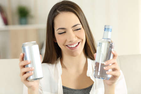 Front view portrait of a happy woman deciding between water or soda refreshment sitting on a couch in the living room at home Stock Photo