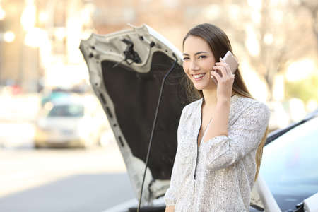 Happy driver calling insurance about a car breakdown and looking at you on the street Stock Photo