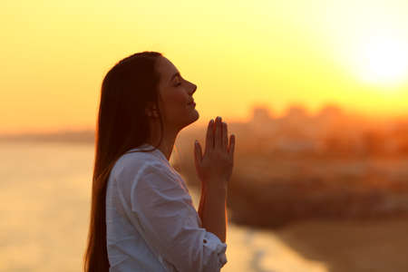 Side view backlight portrait of a woman praying and looking above at sunset