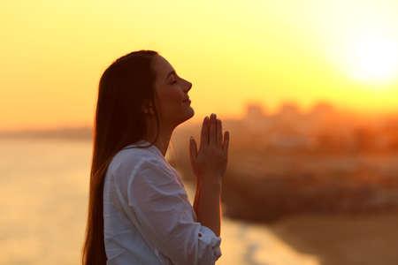 夕暮れ時に祈り、上を見る女性の側面のバックライトの肖像画 写真素材