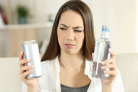 Front view portrait of a confused girl deciding between soda refreshment and water bottle at home Stock Photo