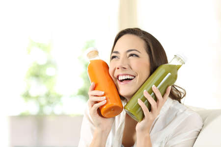 Happy woman loving her vegetable juices looking above sitting on a couch in the living room at home