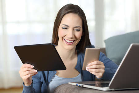 Happy woman using multiple devices on a couch in the living room at home Stock Photo