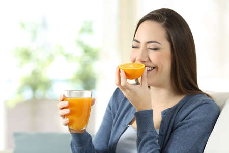 Happy woman smelling an orange and holding a juice sitting on a couch in the living room at home
