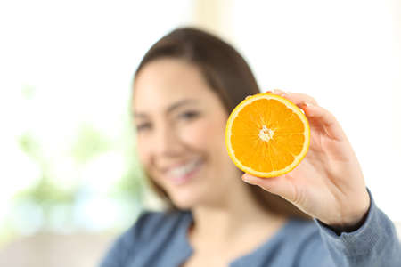 Happy woman showing an orange sitting on a couch in the living room at home Stok Fotoğraf
