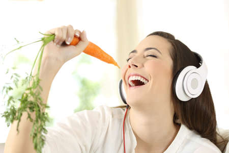 Cheerful girl wearing headphones singing using a carrot as a microphone at home Stok Fotoğraf - 95430136