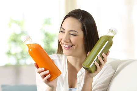 Happy woman comparing two vegetable juices sitting on a couch in the living room at home