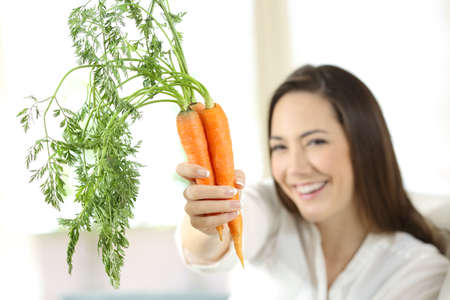 Happy woman showing a bundle of carrots sitting on a couch in the living room at home