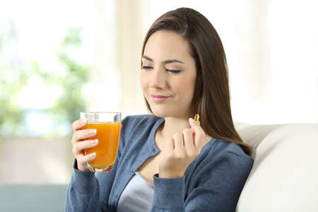Woman holding an orange juice and vitamin pill sitting on a couch in the living room at home Banco de Imagens - 95430134