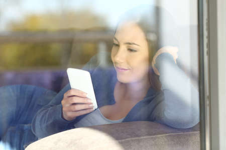Serious woman relaxing reading phone messages sitting on a couch in the living room at home