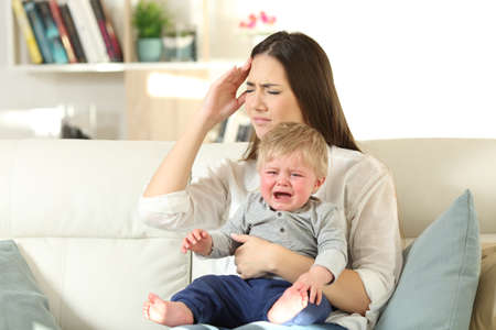 Mother suffering and baby crying desperately sitting on a couch in the living room at home Фото со стока