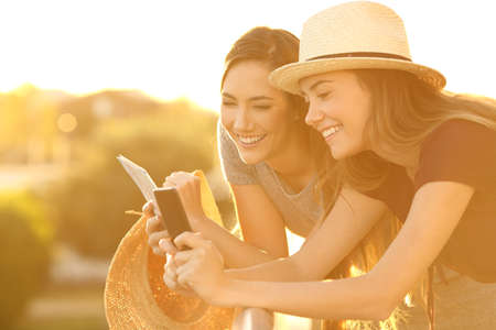 Two happy tourists planning vacations with a smart phone and a guide in an hotel balcony Stock Photo
