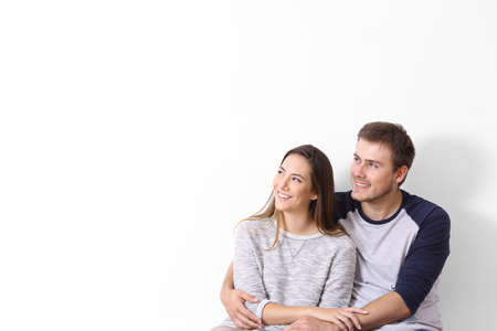 Front view of a happy couple looking at side on a white wall Reklamní fotografie