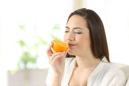 Happy woman smelling half orange sitting on a couch in the living room at home