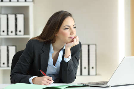 Distracted and bored businesswoman ready to sign a contract thinking looking away at office Reklamní fotografie