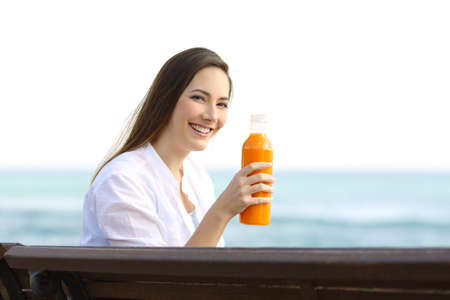 Happy woman holding an orange juice bottle sitting on a bench on the beach