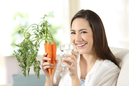 Happy woman holding carrots and a water glass looking at camera sitting on a couch in the living room at home Stok Fotoğraf
