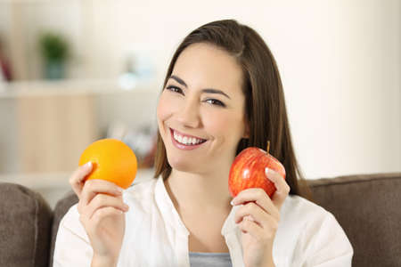 Front view portrait of a happy woman holding an apple and orange looking at camera sitting on a couch in the living room at home