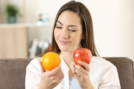 Front view portrait of a doubtful woman deciding between an orange and apple sitting on a couch at home Banco de Imagens - 96724955