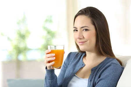 Serious woman holding a glass of orange juice sitting on a couch in the living room at home