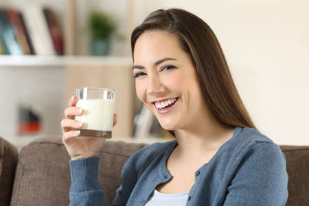 Portrait of a happy woman holding a glass of milk looking at camera sitting on a couch in the living room at home