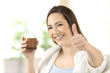Happy woman holding a cocoa drink on a glass looking at camera sitting on a couch in the living room at home Reklamní fotografie
