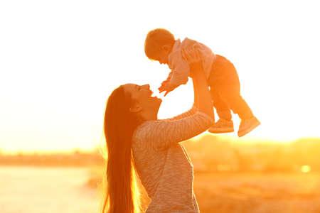 Backlight side view portrait of a happy mother raising her kid son at sunset Reklamní fotografie