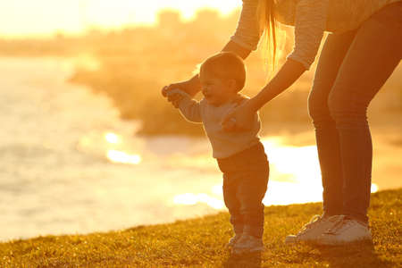Side view of a kid learning to walk and mother helping him on the grass outdoors at sunset with a city in the background