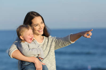 Happy mother and kid laughing and pointing horizon on the beach in a sunny day