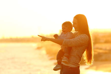 Backlight portrait of a silhouette of a happy mother and kid looking away at sunset on the beach