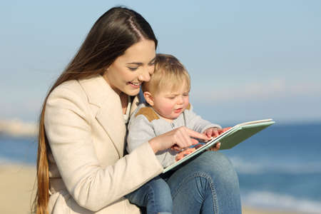 Kid learning and mother showing a book outdoors on the beach in a sunny day Reklamní fotografie