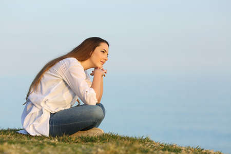 Relaxed woman thinking and looking away sitting on the grass on the beach Stock Photo