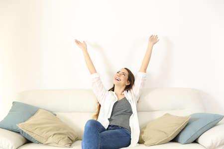 retrato de ángulo ancho de una mujer feliz levantando los brazos y mirando a través de un sofá con un espacio de copia