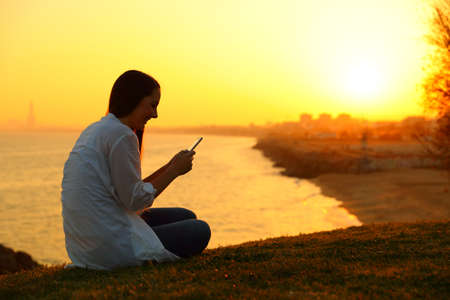 Side view backlight portrait of a girl using a smart phone in a beautiful sunset Reklamní fotografie