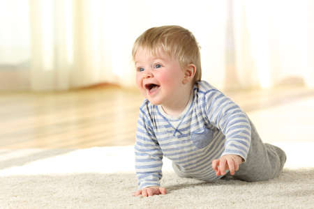 Happy baby boy crawling and laughing on the floor at home Reklamní fotografie