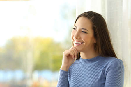 Portrait of a smiley woman thinking and looking at side  near a window at home Stock Photo