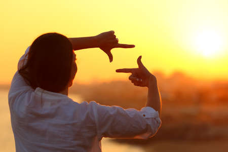 Back view backlight portrait of a woman framing with fingers at sunset Reklamní fotografie