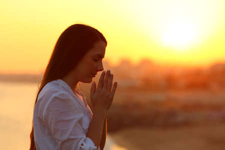 Side view backlight portrait of a single woman praying and looking down at sunset