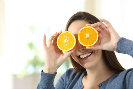 Happy woman joking with two half orange slices sitting on a couch in the living room at home
